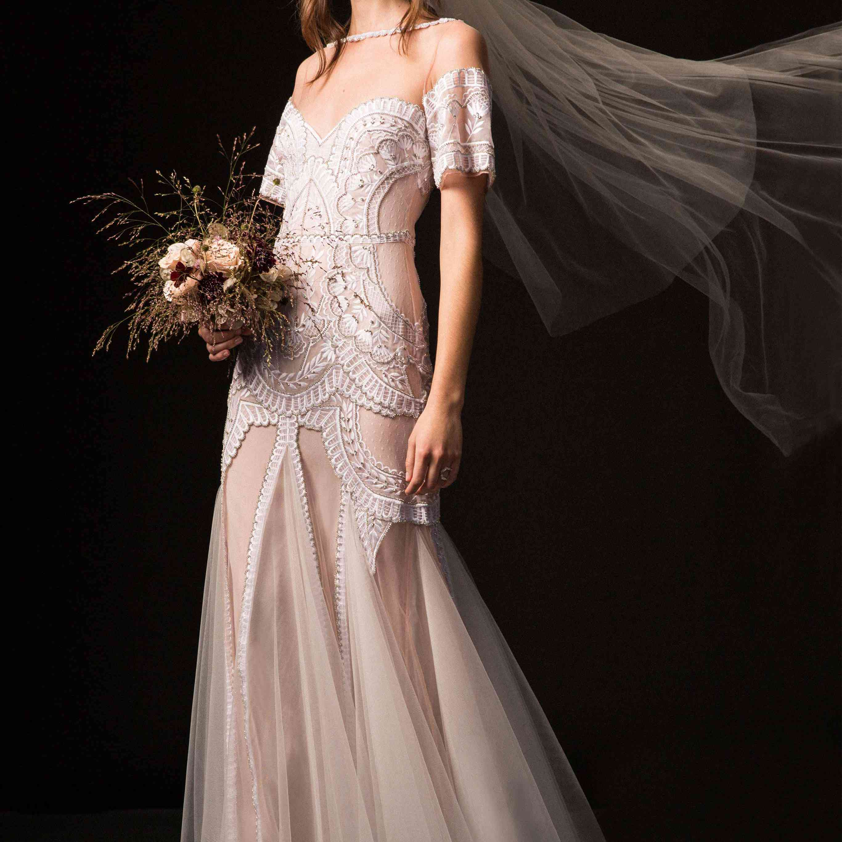 Model in embroidered tulle dress with illusion neckline and off-the-shoulder sleeves.
