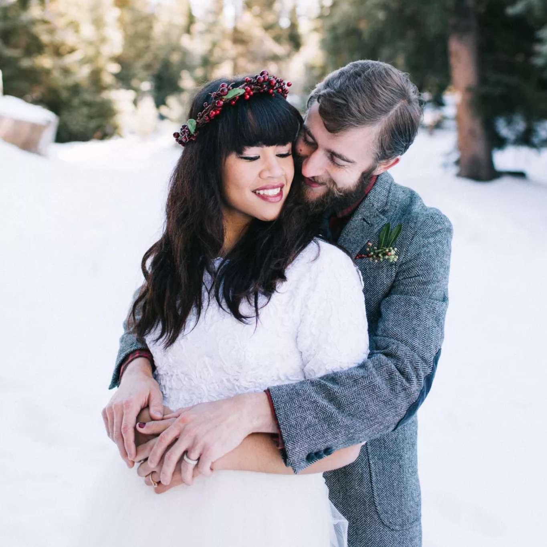 Groom hugs bride with red berry crown