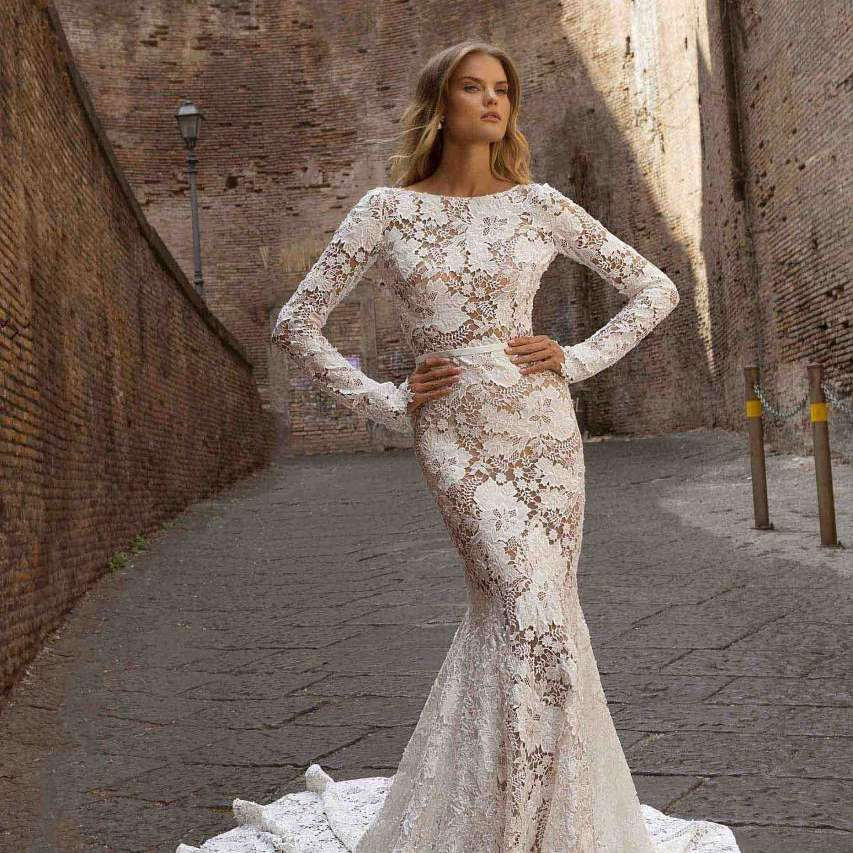 Model in long sleeve allover lace illusion gown