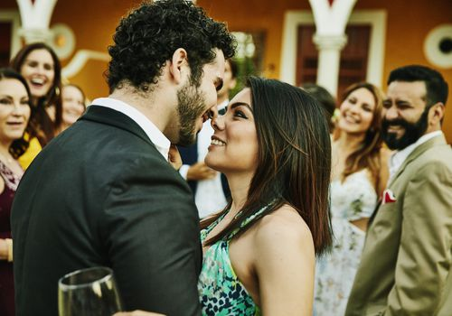 Smiling and embracing couple about to kiss during outdoor wedding reception