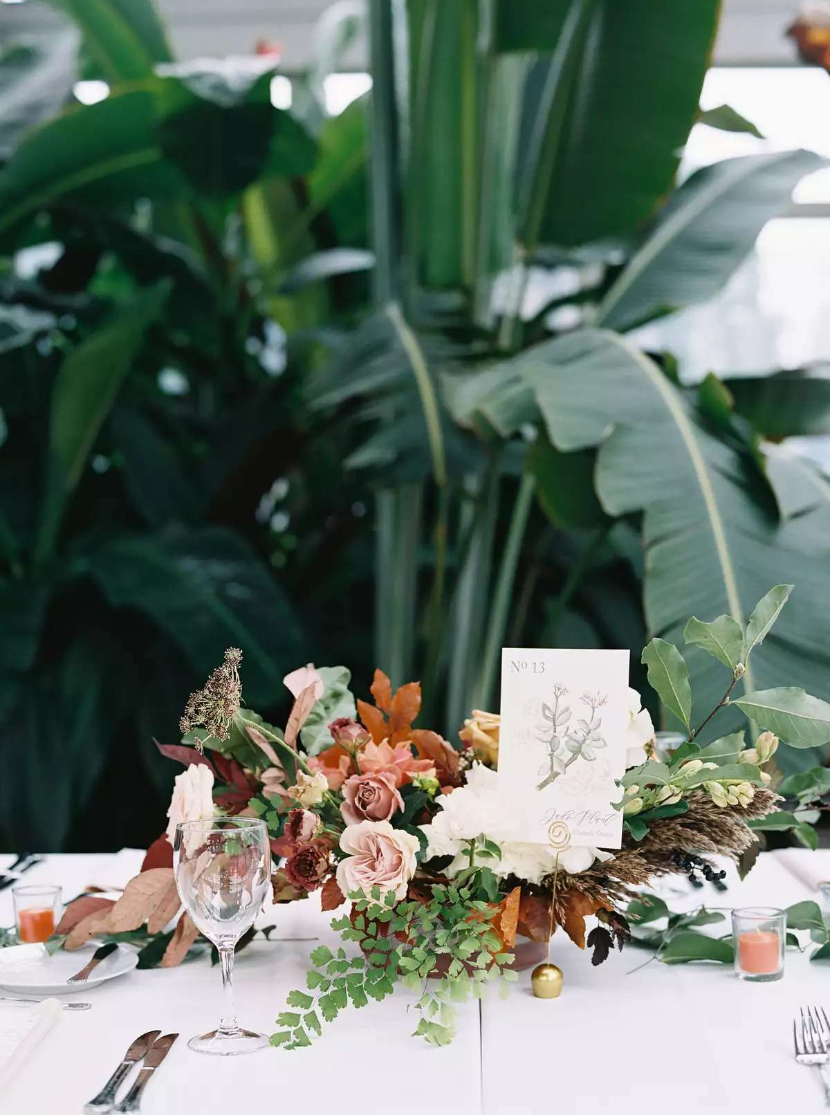 Botanical backdrop with head table featuring autumnal flower arrangment