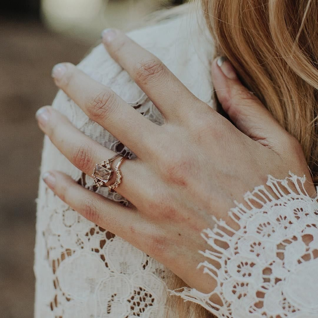 Bride's hand on shoulder with a rectangle ring stack on finger