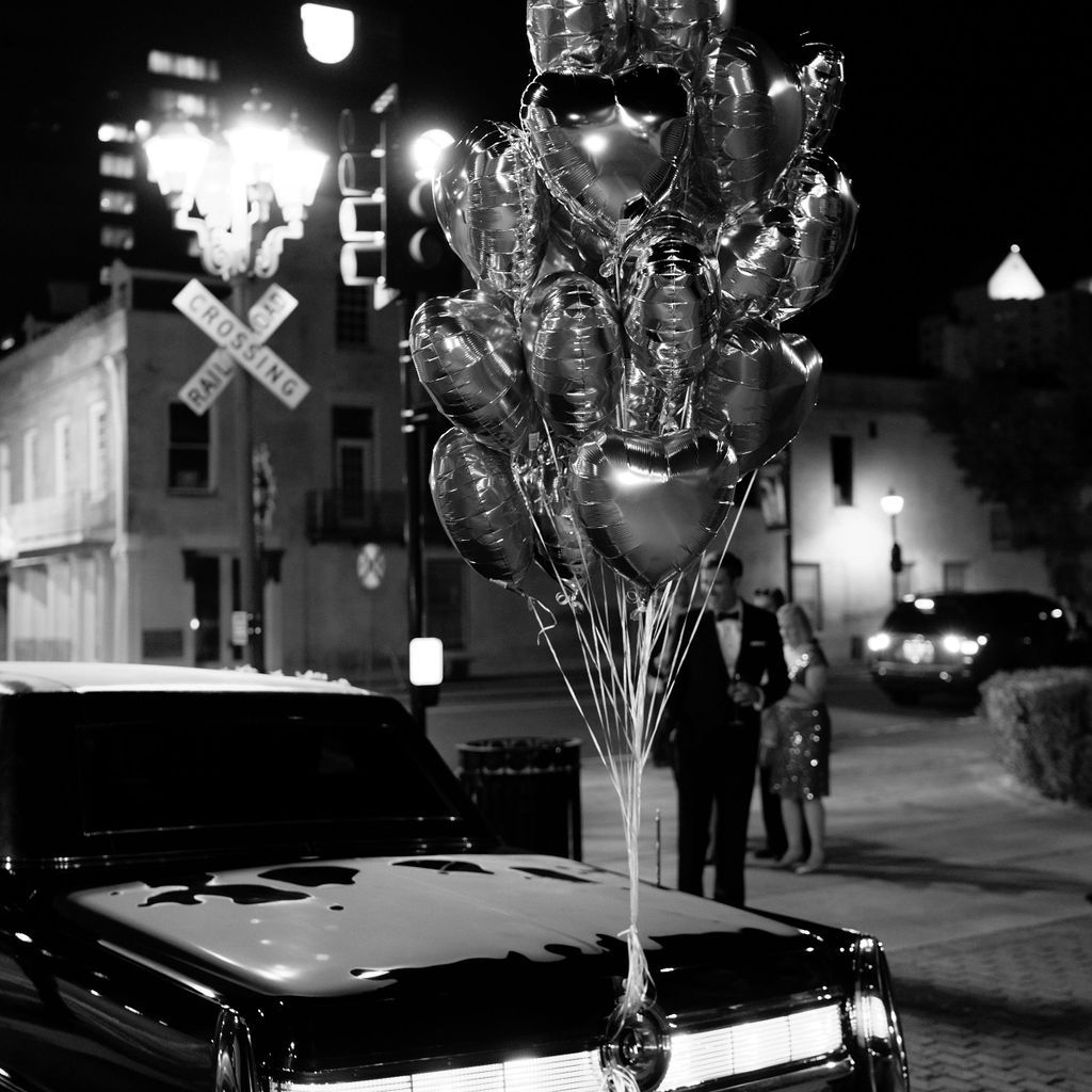Getaway car with a bunch of heart-shaped metallic balloons fastened to the back