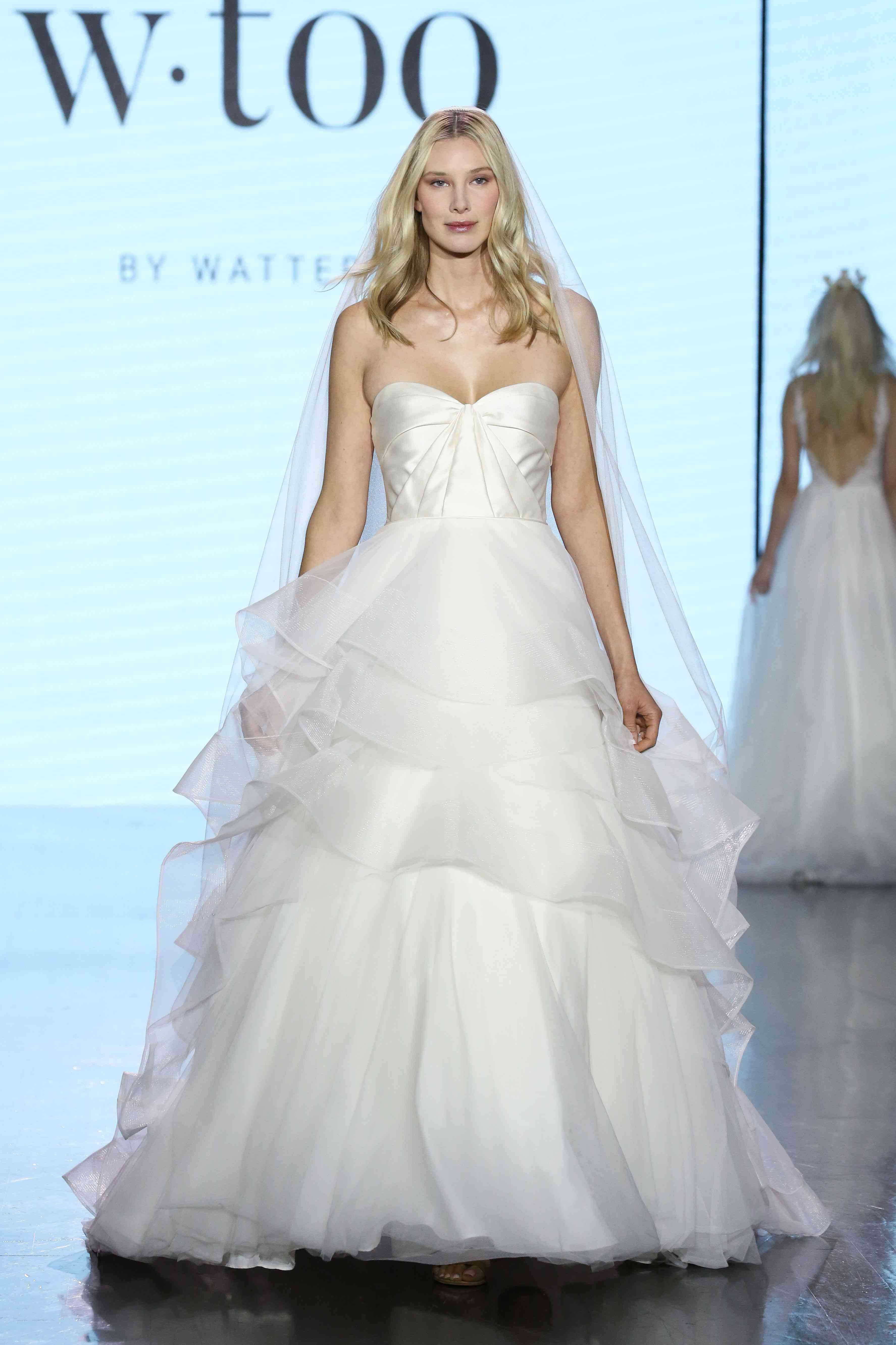 Model in strapless ballgown with a ruched satin bodice and a multi-tiered organza skirt
