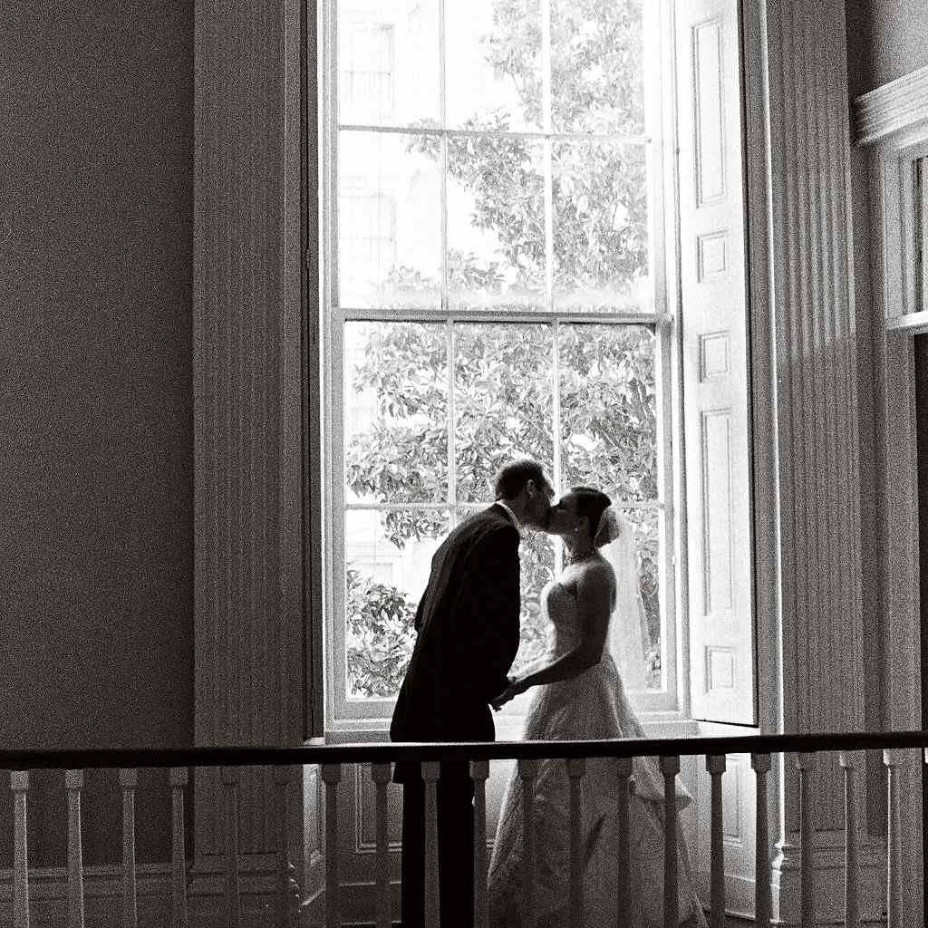 A black and white photo captures a couple kissing in front of a window on their wedding day