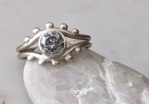 Round salt and pepper diamond in split band engagement ring