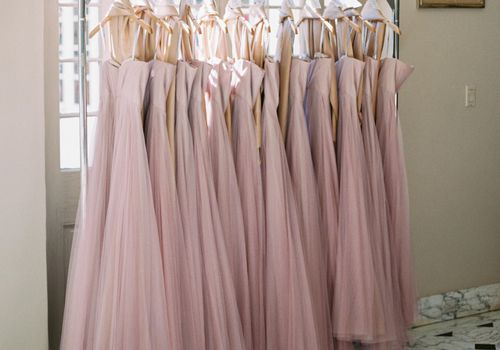 Row of pink dresses hanging on a garment rack