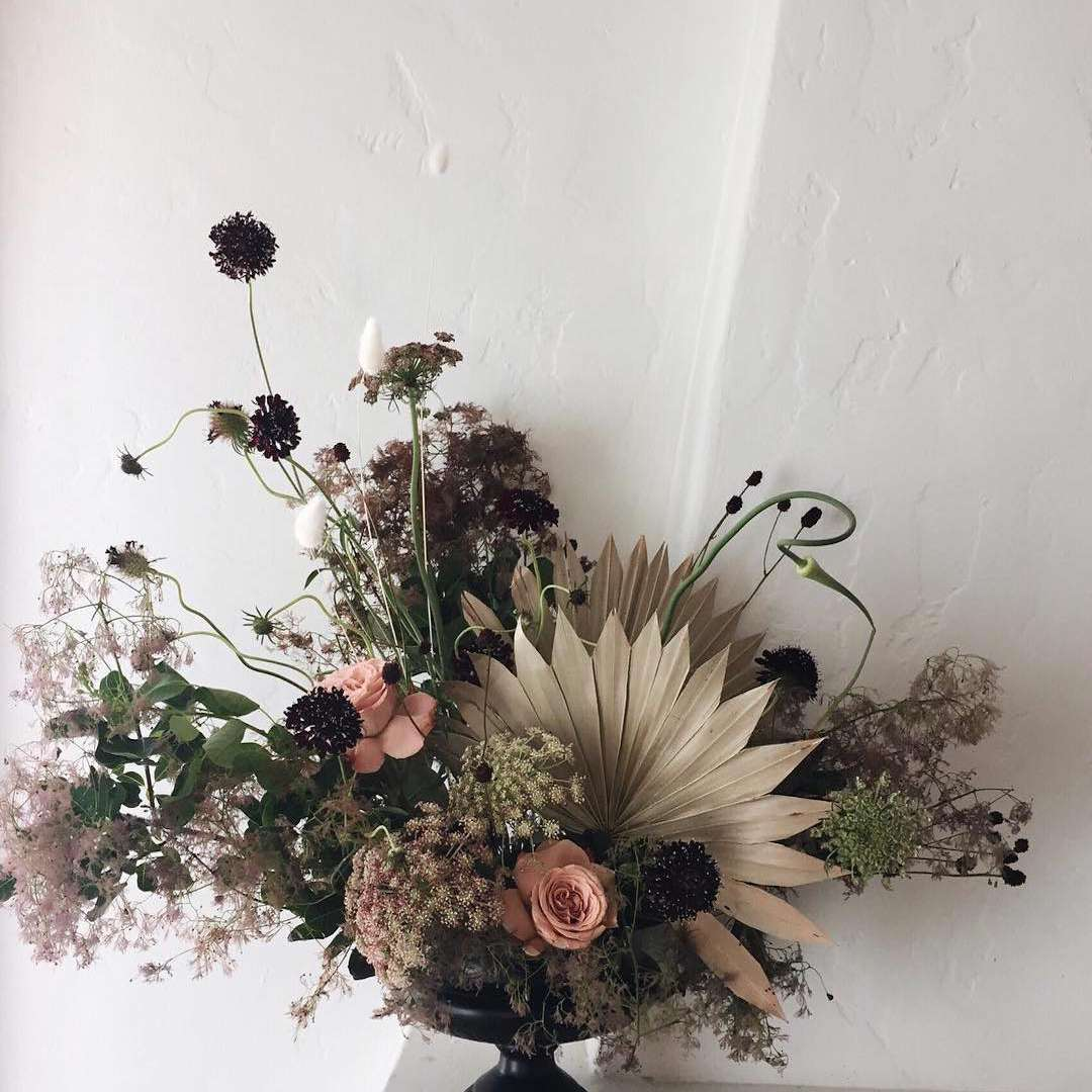 Centerpiece of dried fan palms, Queen Anne's lace, scabiosa, smokebush, and garden roses