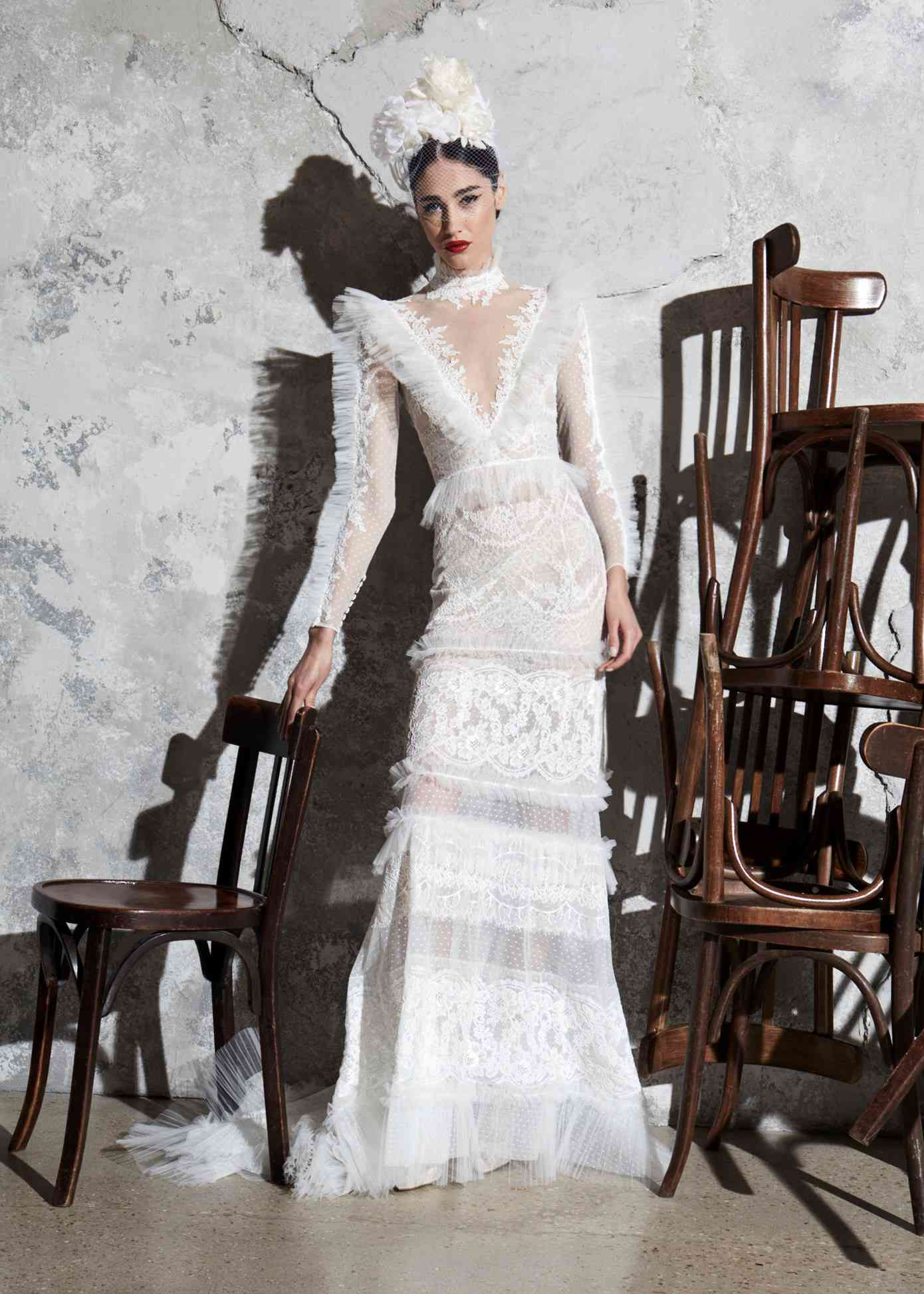 Model in a lace-embroidered tulle gown with a high neck and pleated tulle neckline, sleeves, skirt, waist, and hem