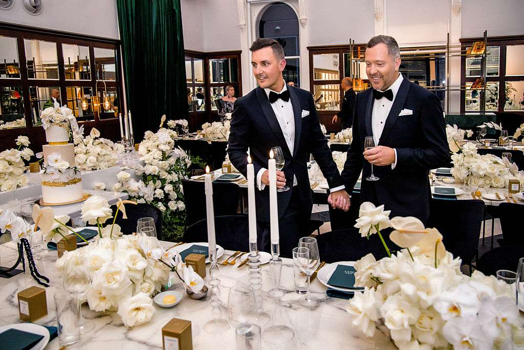 grooms looking at reception decor