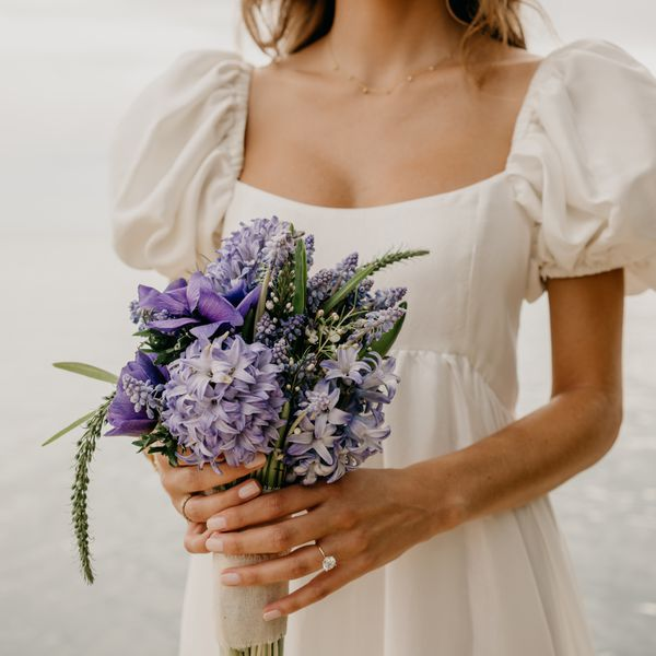 bride holding a bouquet of hyacinths and anemones