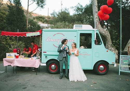 Bride and groom eating snow cones in front of blue food truck
