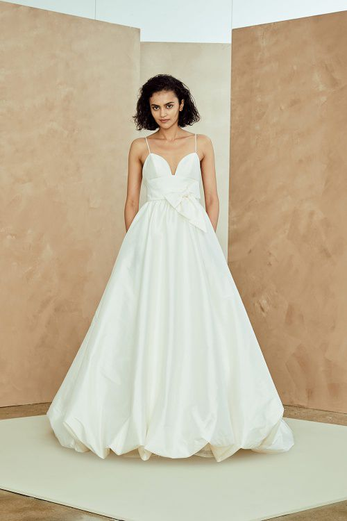 Model in plunge neck and bubble skirt white wedding gown