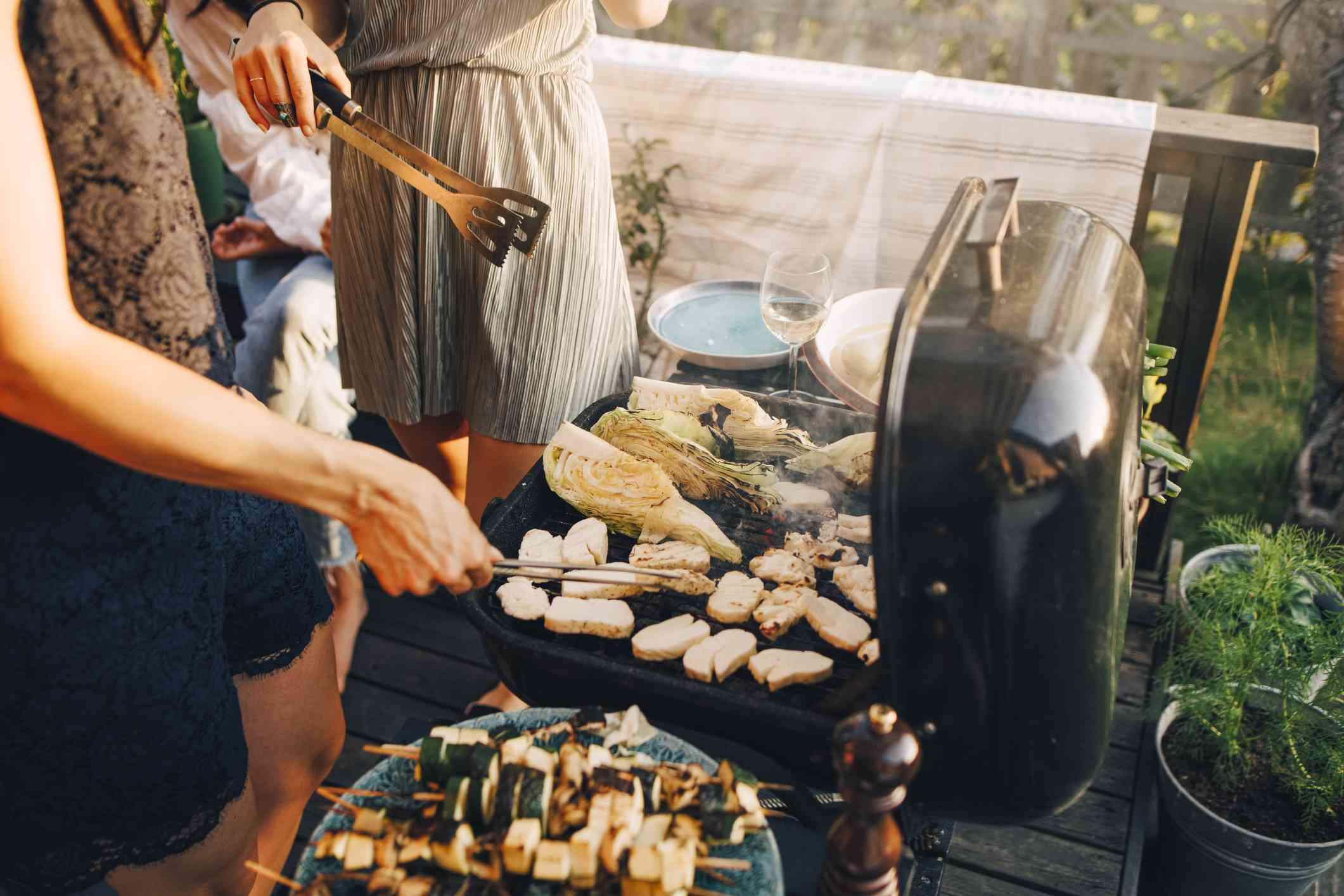 Midsection of female friends grilling food on barbecue grill