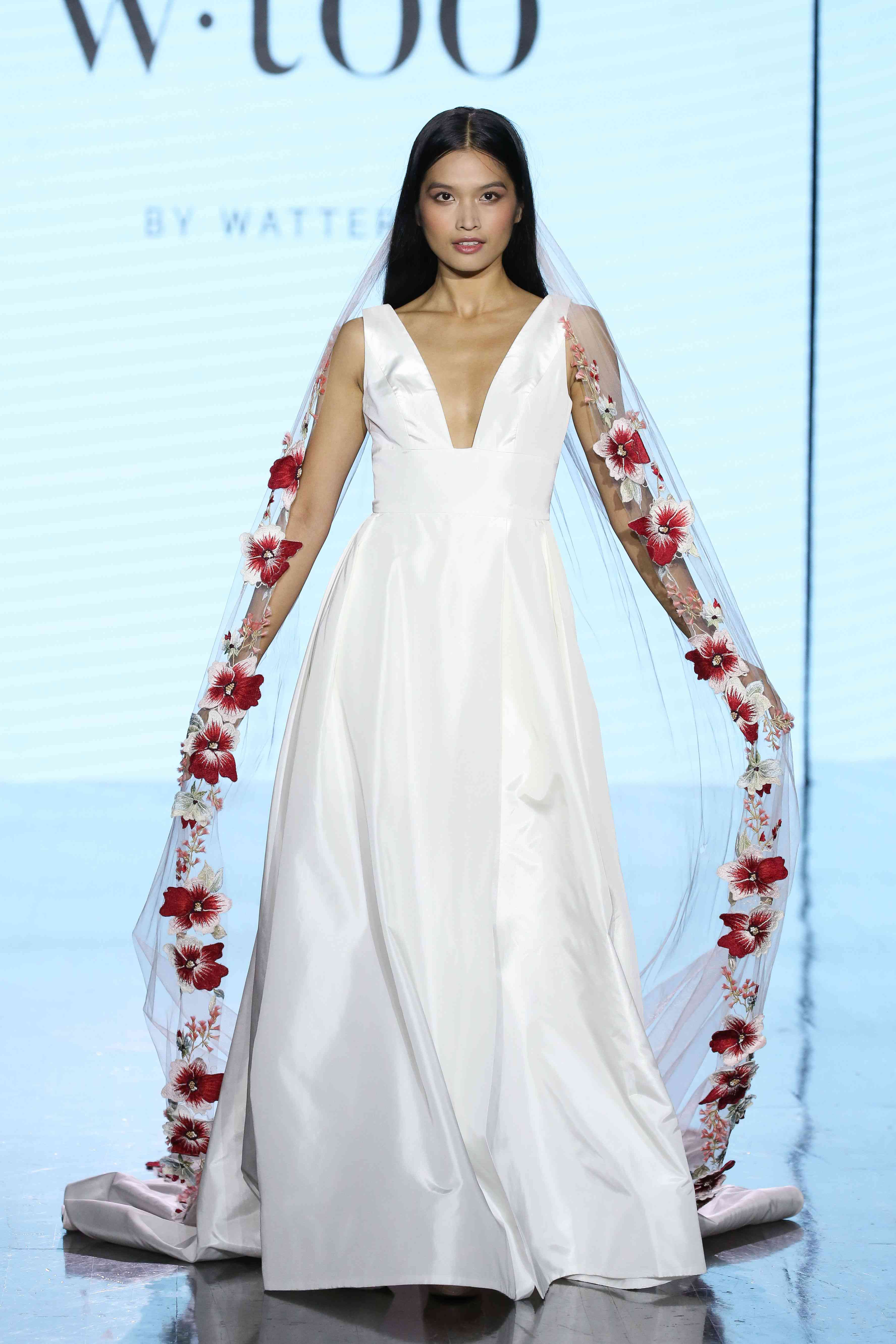 Model in sleeveless satin wedding gown with a plunging neckline and banded waist