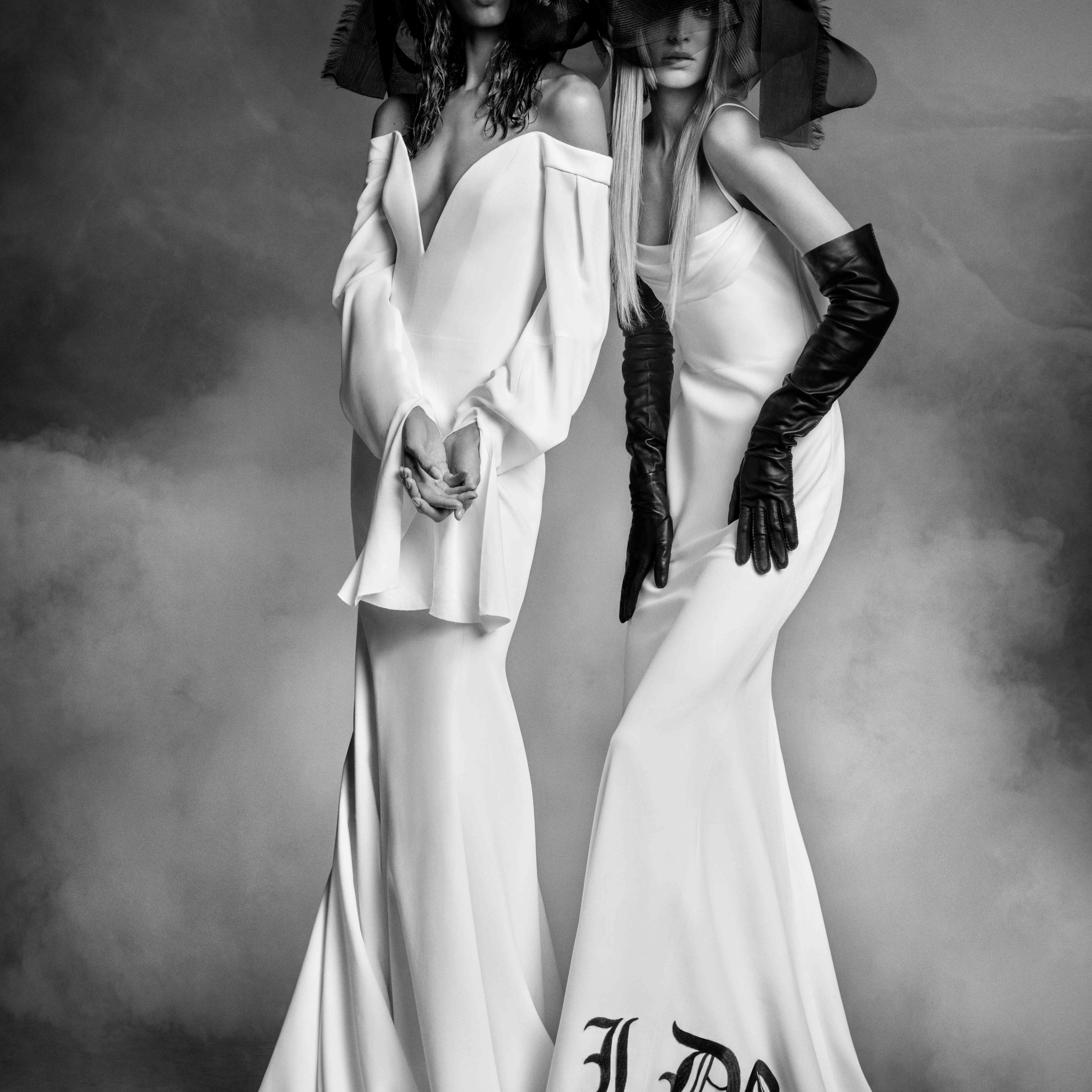 Two models in long white wedding gowns with black headpieces