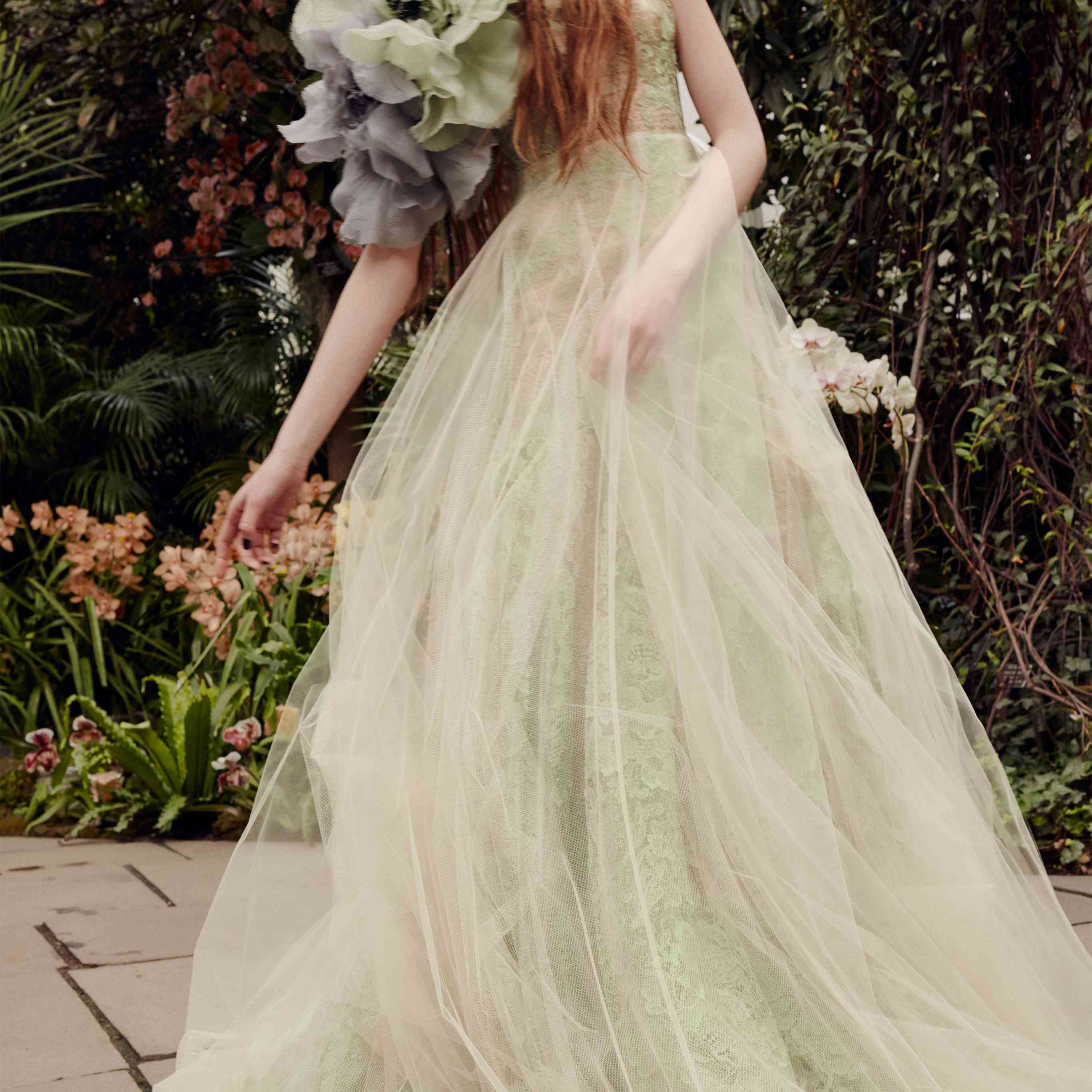 Model in a sage and nude tulle A-line gown with gray and sage flower accents at the shoulder