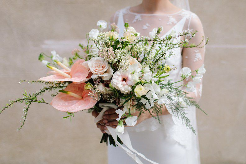 Bride holding bouquet of pale pink anthurium and roses, sweet pea, wispy fern, and rice flowers