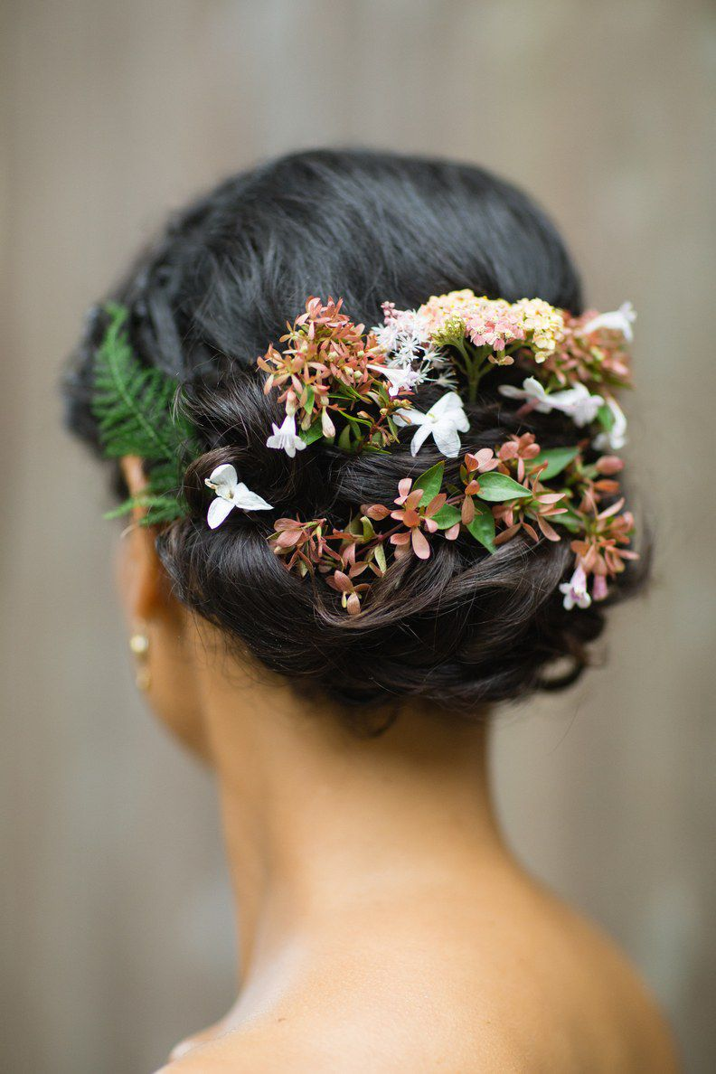 Woven updo with flowers tucked into it