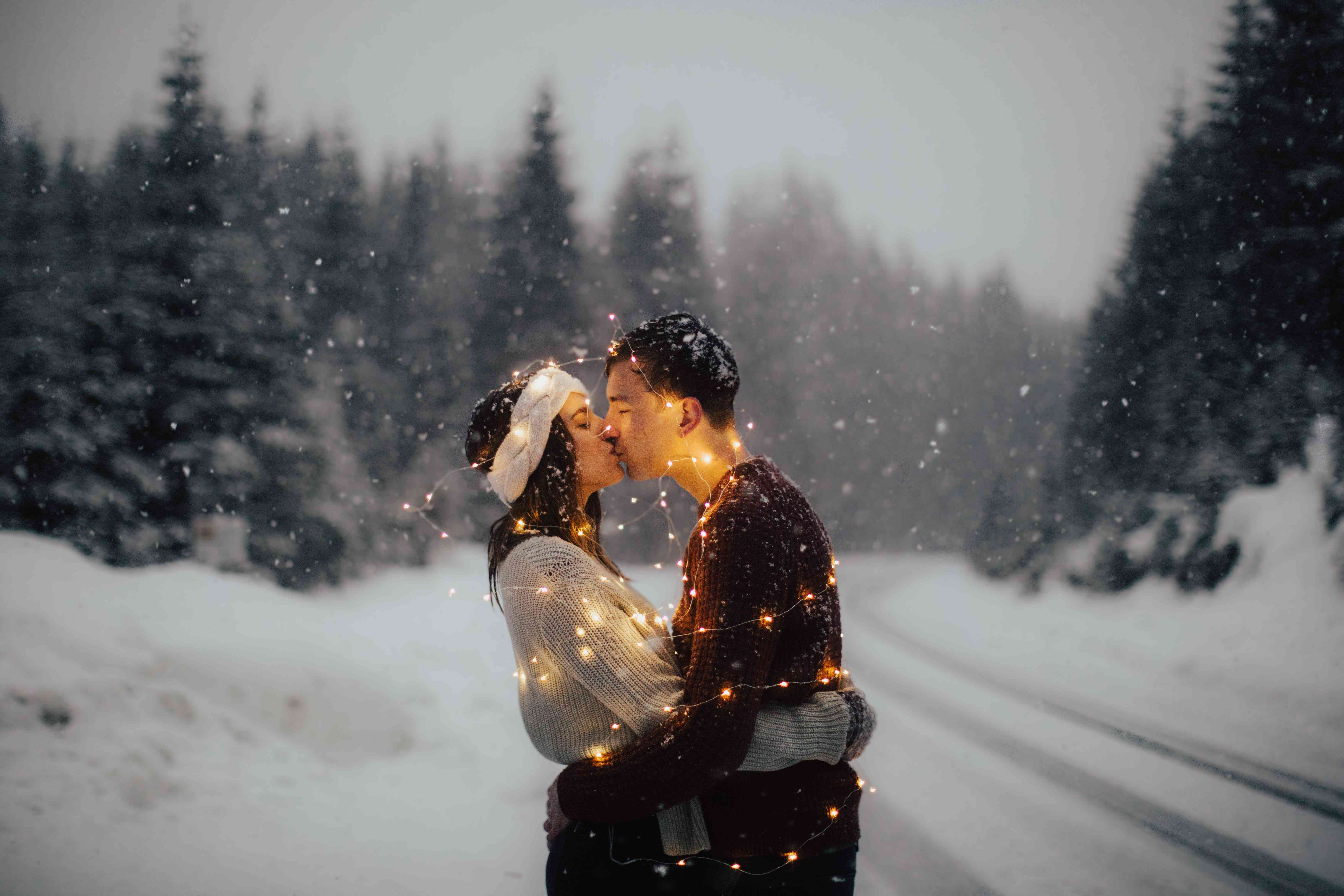 Couple with fairy lights in the snow