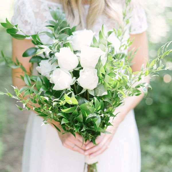 Bride holding bouquet of white roses and greenery