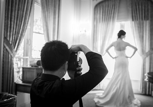 photographer capturing bride by window
