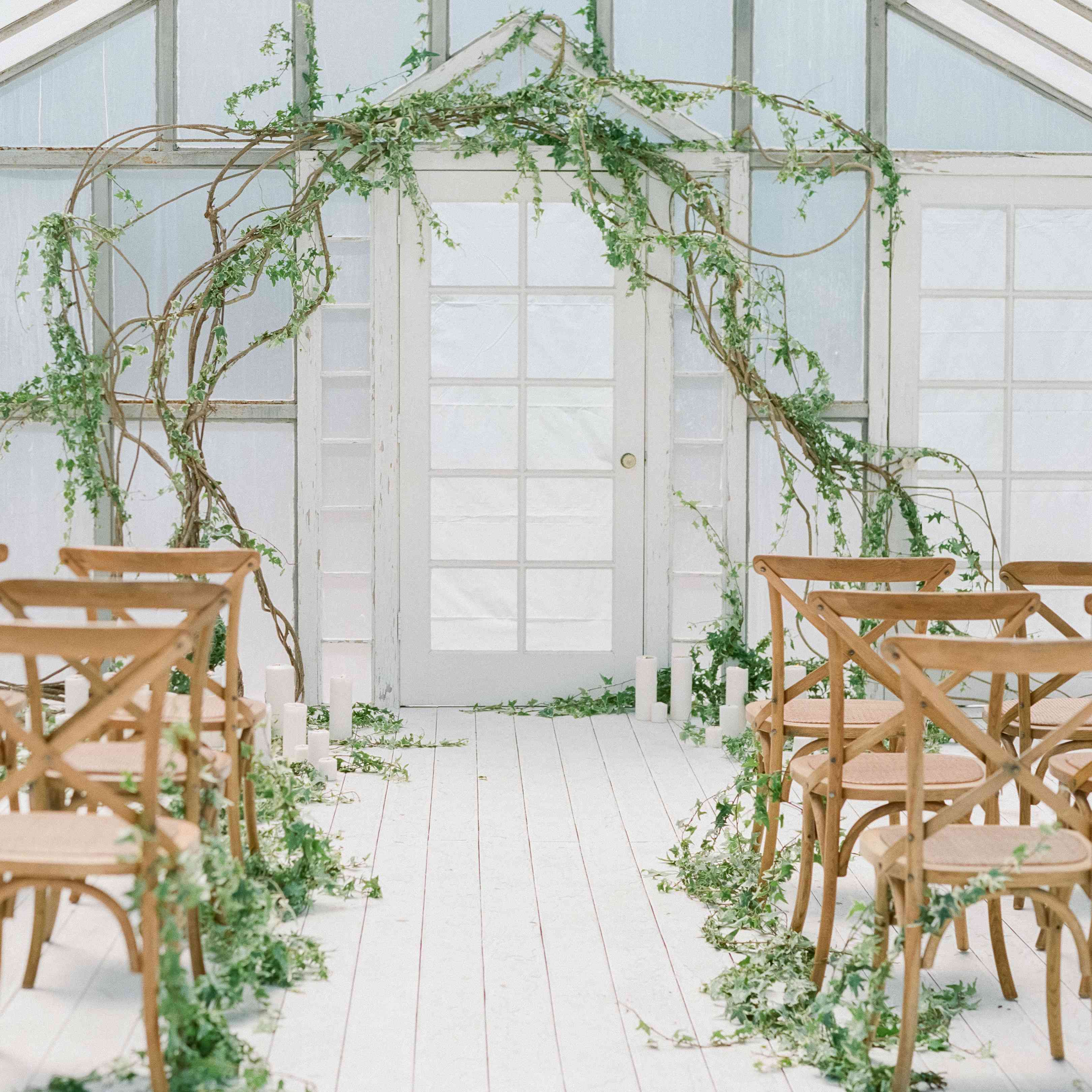 Wedding aisle with white wood floors and greenery on each side and a greenery, branch arch