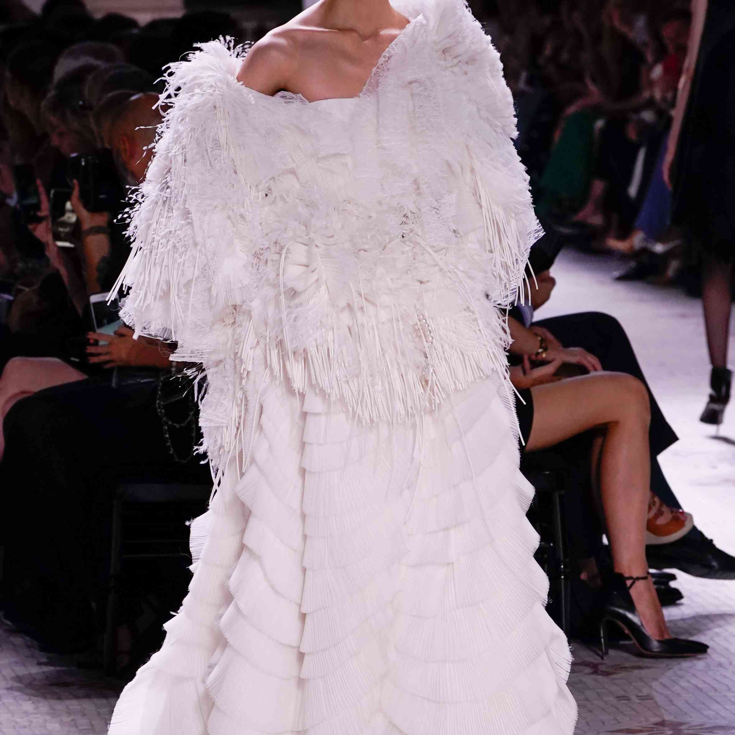 A model walks the runway in feathered, tiered white gown
