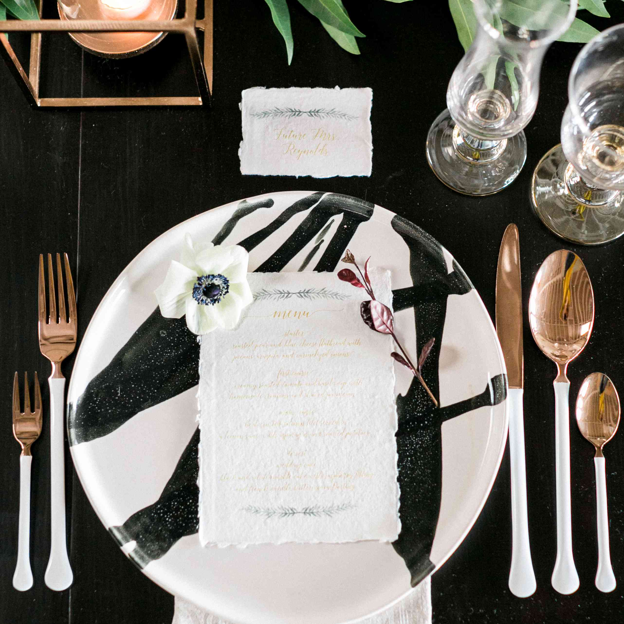 Black and white party tablescape with rose gold silverware and greenery garland