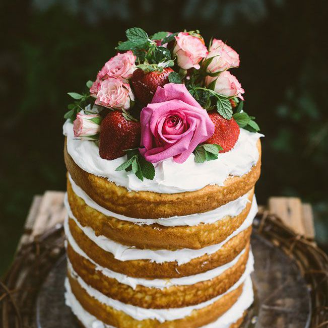 Naked cake with white frosting and pink flowers