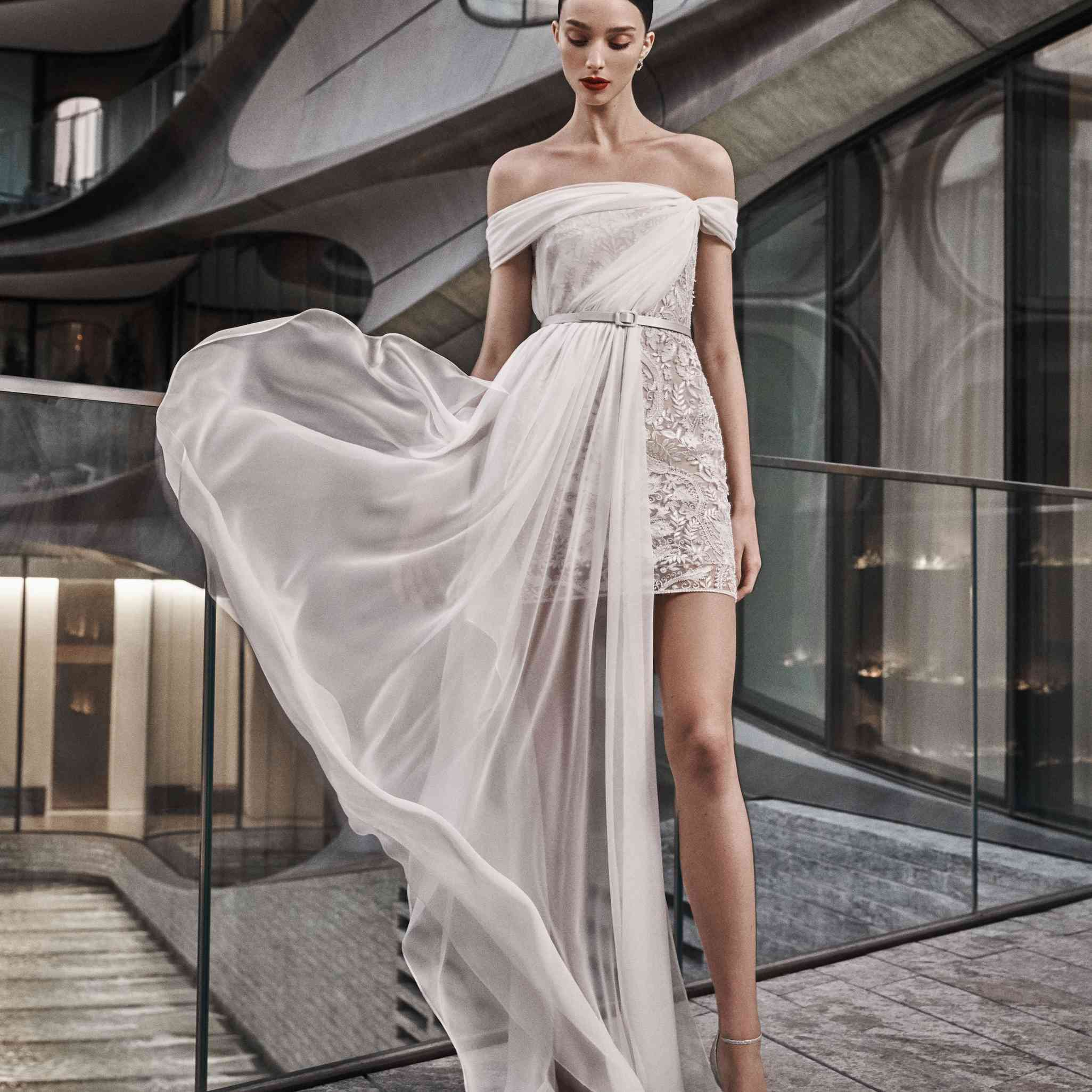 Model in off-the-shoulder embroidered mini dress with chiffon draping.