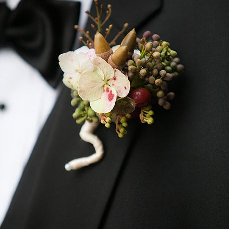 A white and green boutonniere comprised of hydrangea blossoms, berries, and acorns, created by Martha's Gardens
