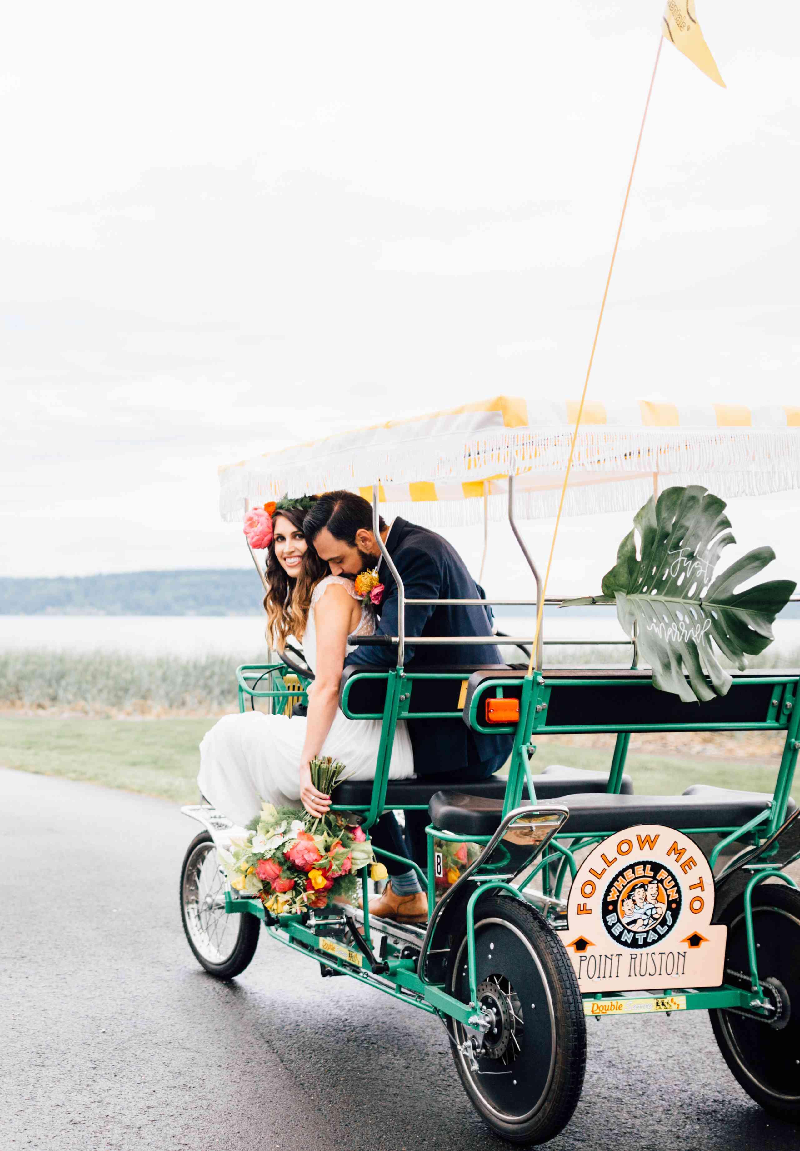 Bride and groom in a open cart getaway car