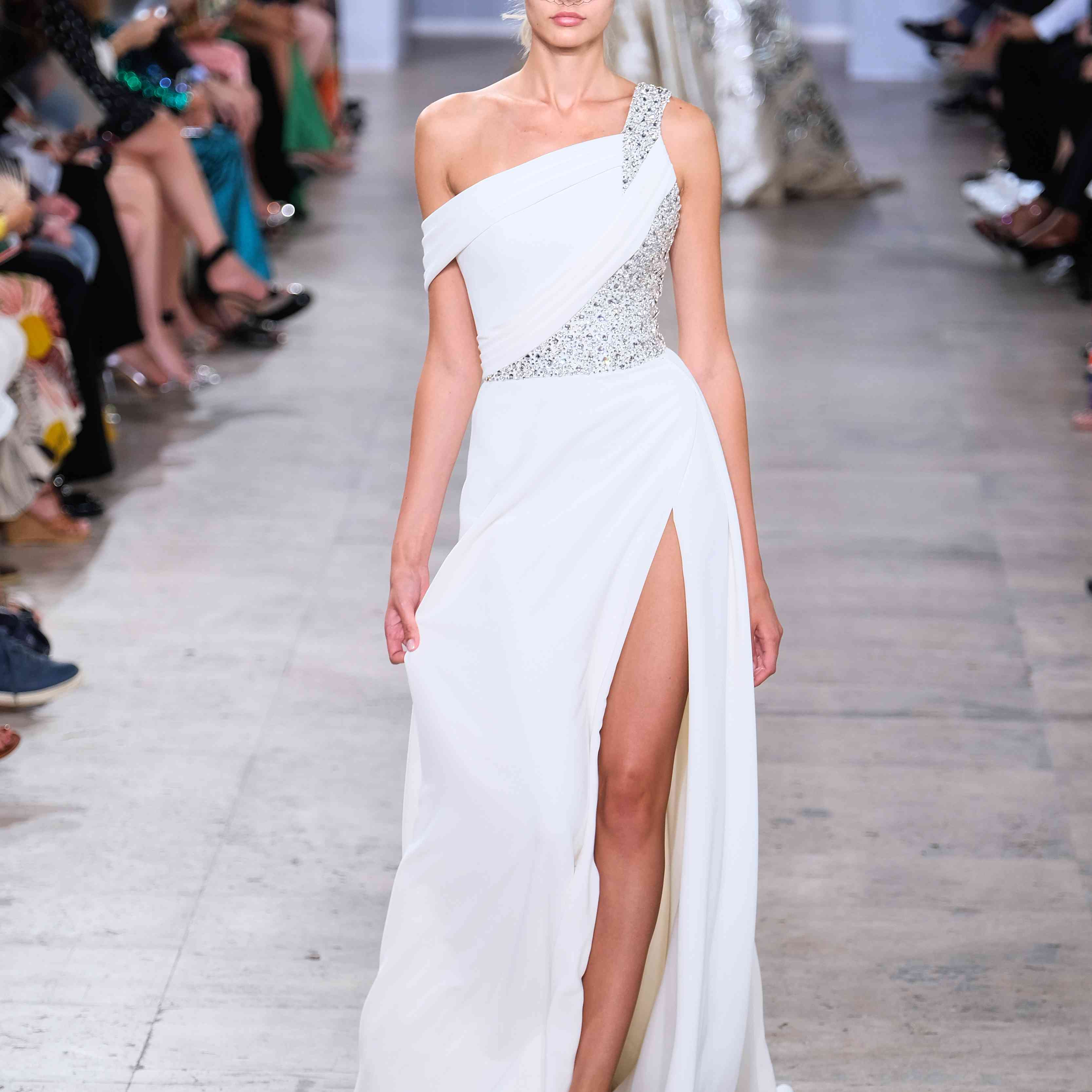 Model in one-shouldered white gown with high slit