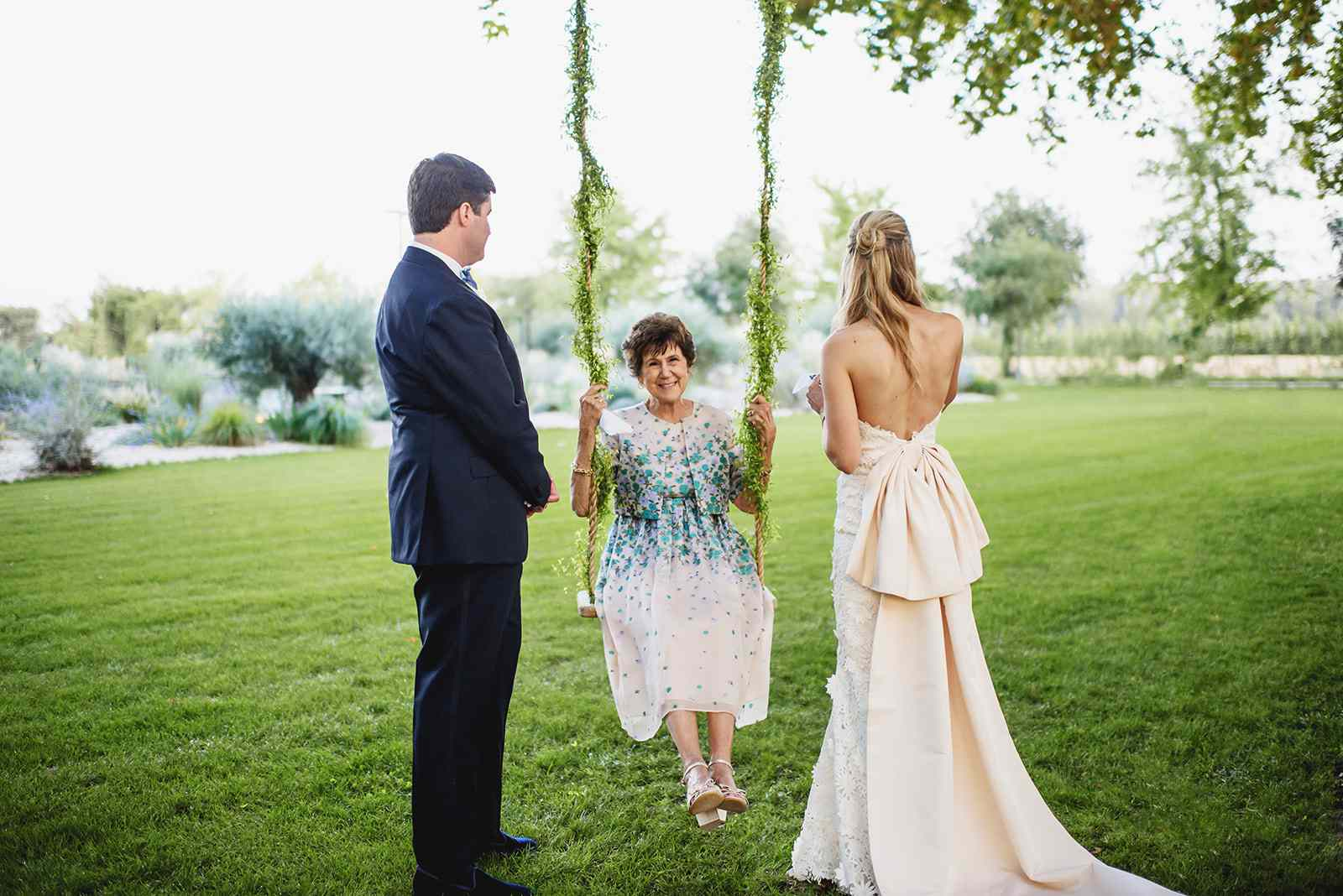 Bride and groom with mom on swing