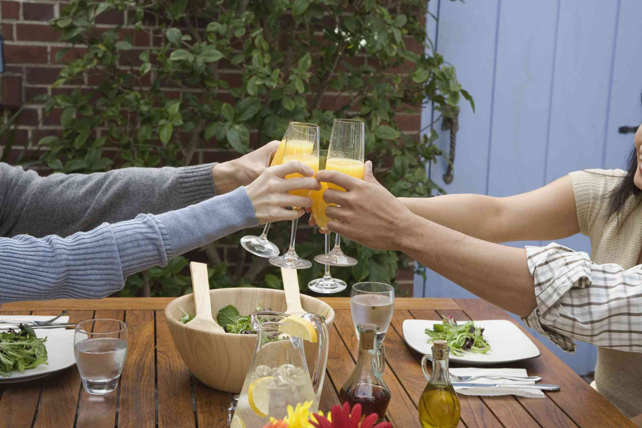 Four people toasting with mimosas