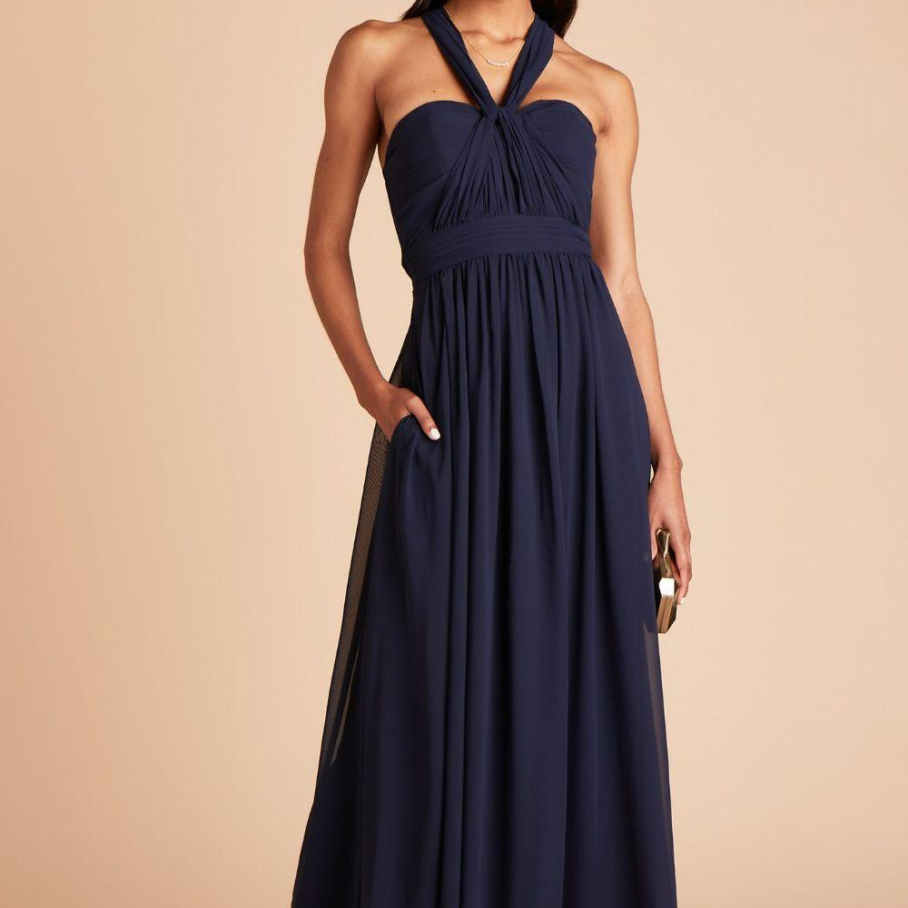 Model in a dark blue A-line gown with a halter neckline