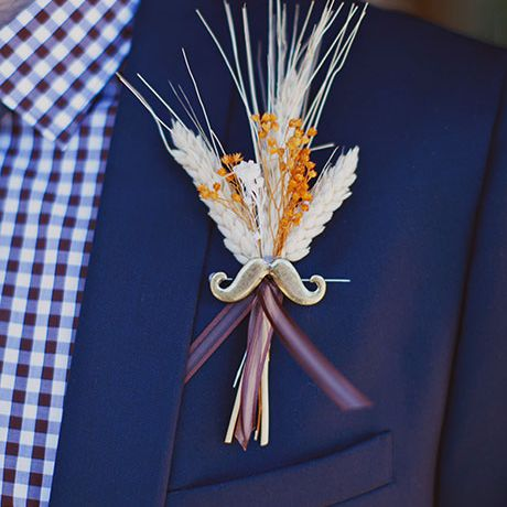 A mustache pin boutonniere accented with dried wheat and flowers