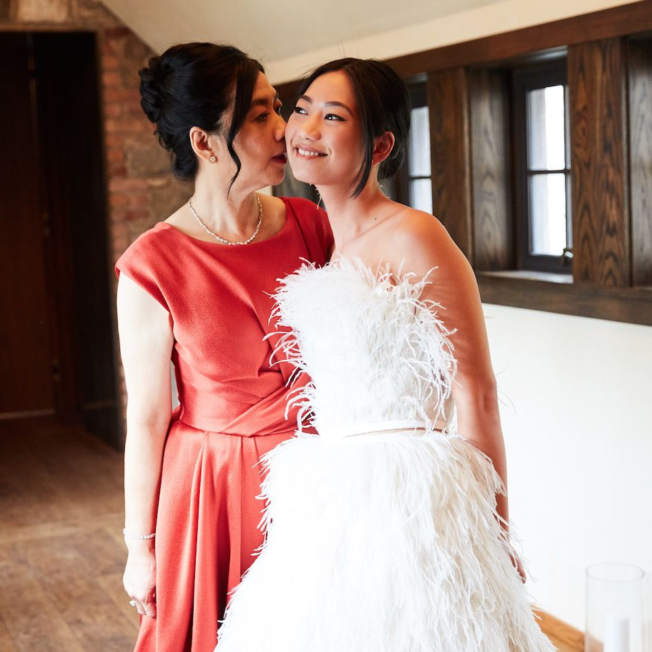 Mother of the bride kissing bride on the cheek