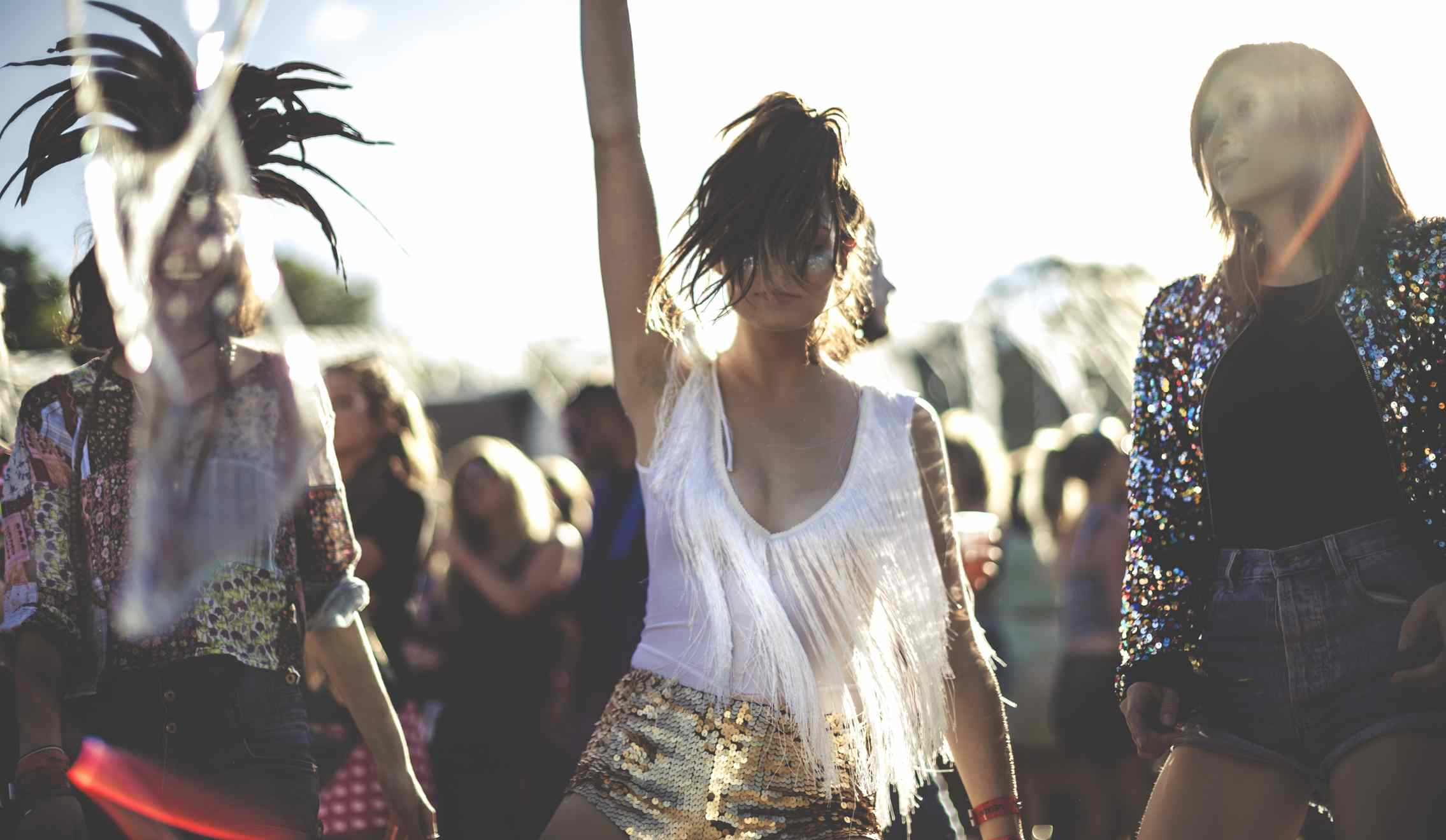 Young woman at a summer music festival wearing golden sequinned hot pants, dancing among the crowd