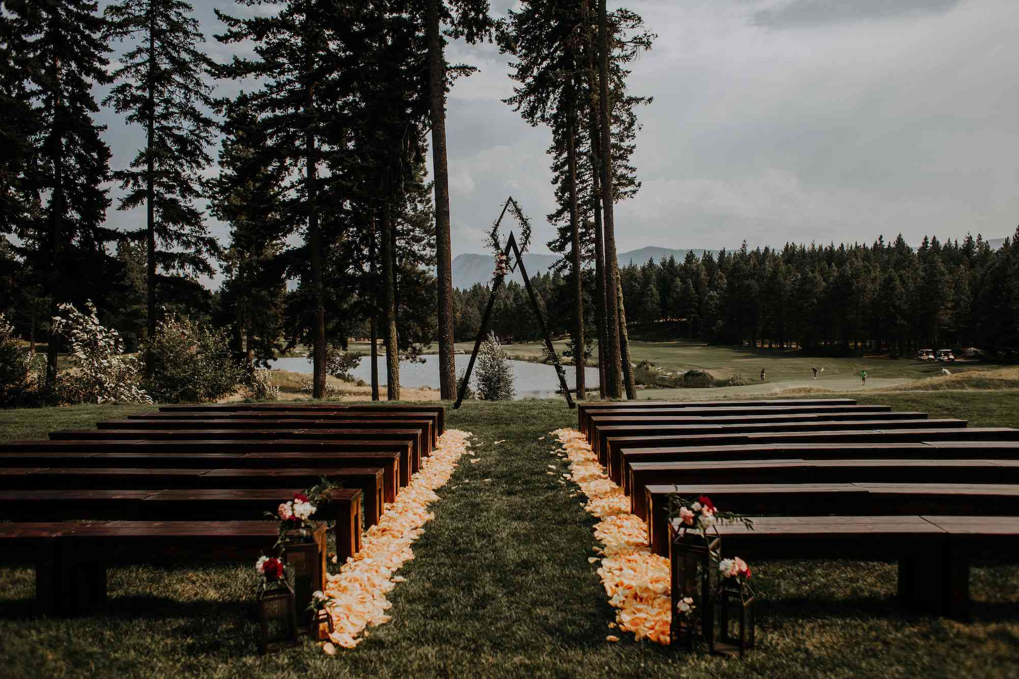 Ceremony with pew benches and bright coral petals lining the aisle to a triangle arch in front of a lake
