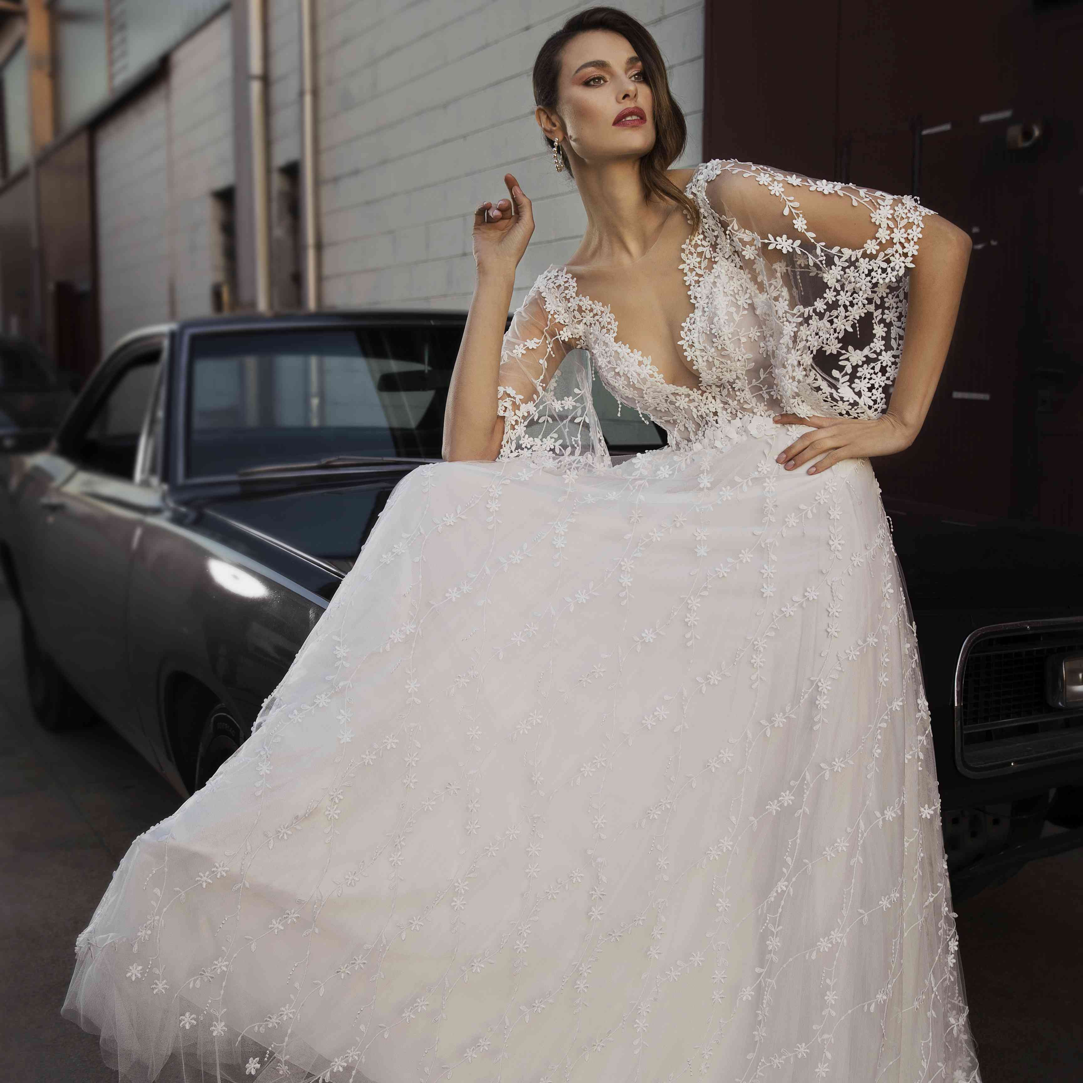 Model sitting on a car in a floral-embroidered tulle gown with an illusion plunging neckline with cascading flutter sleeves