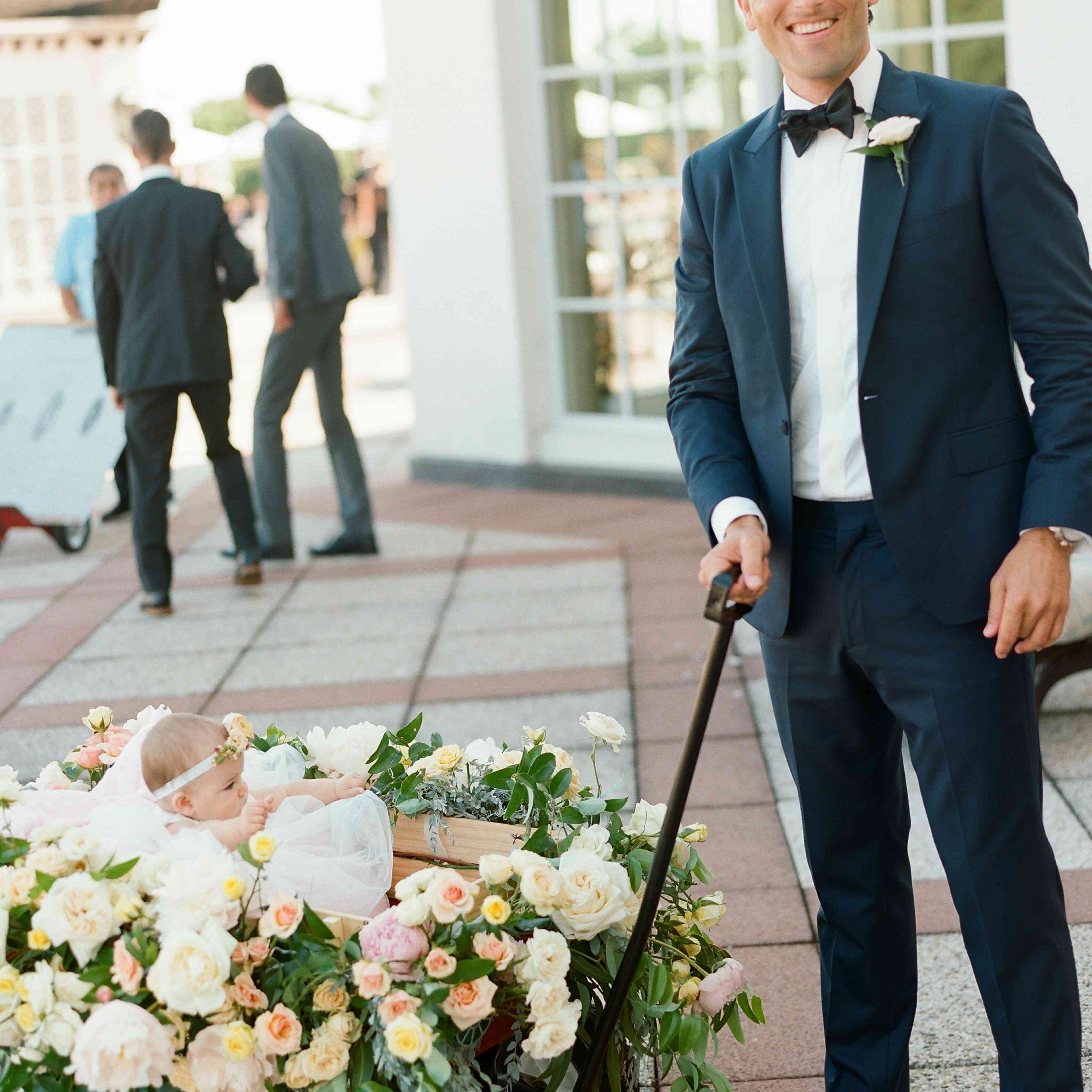 Groom carrying baby in a wagon