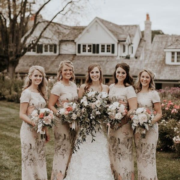 Bridesmaids wearing an assortment of muted floral dresses.