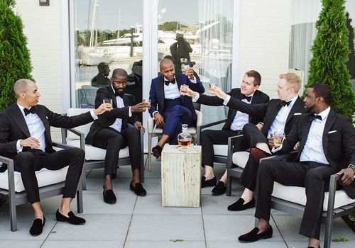 Groom and five groomsmen toasting with Scotch on wedding day