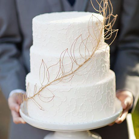 Three-tiered white wedding cake with gold leaf detail