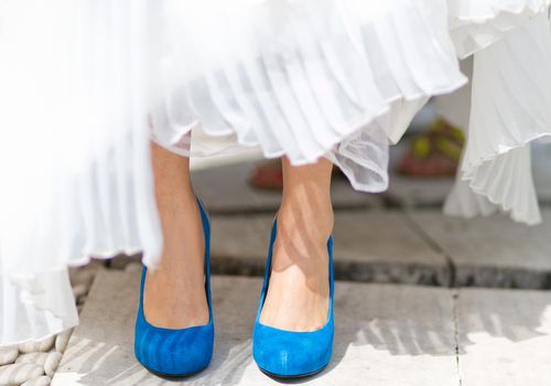 Low section of bride with blue shoes