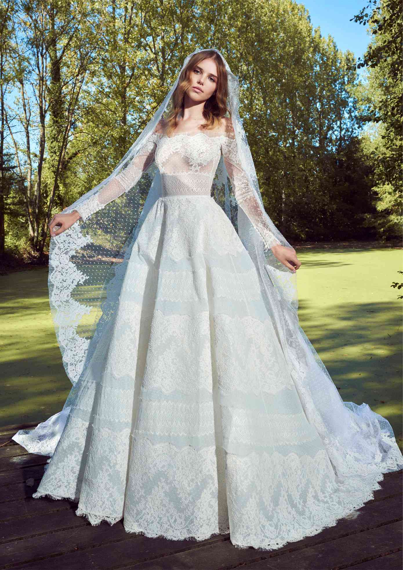 Model in off-the-shoulder long-sleeve dotted tulle ballgown with lace embroidery with a matching veil