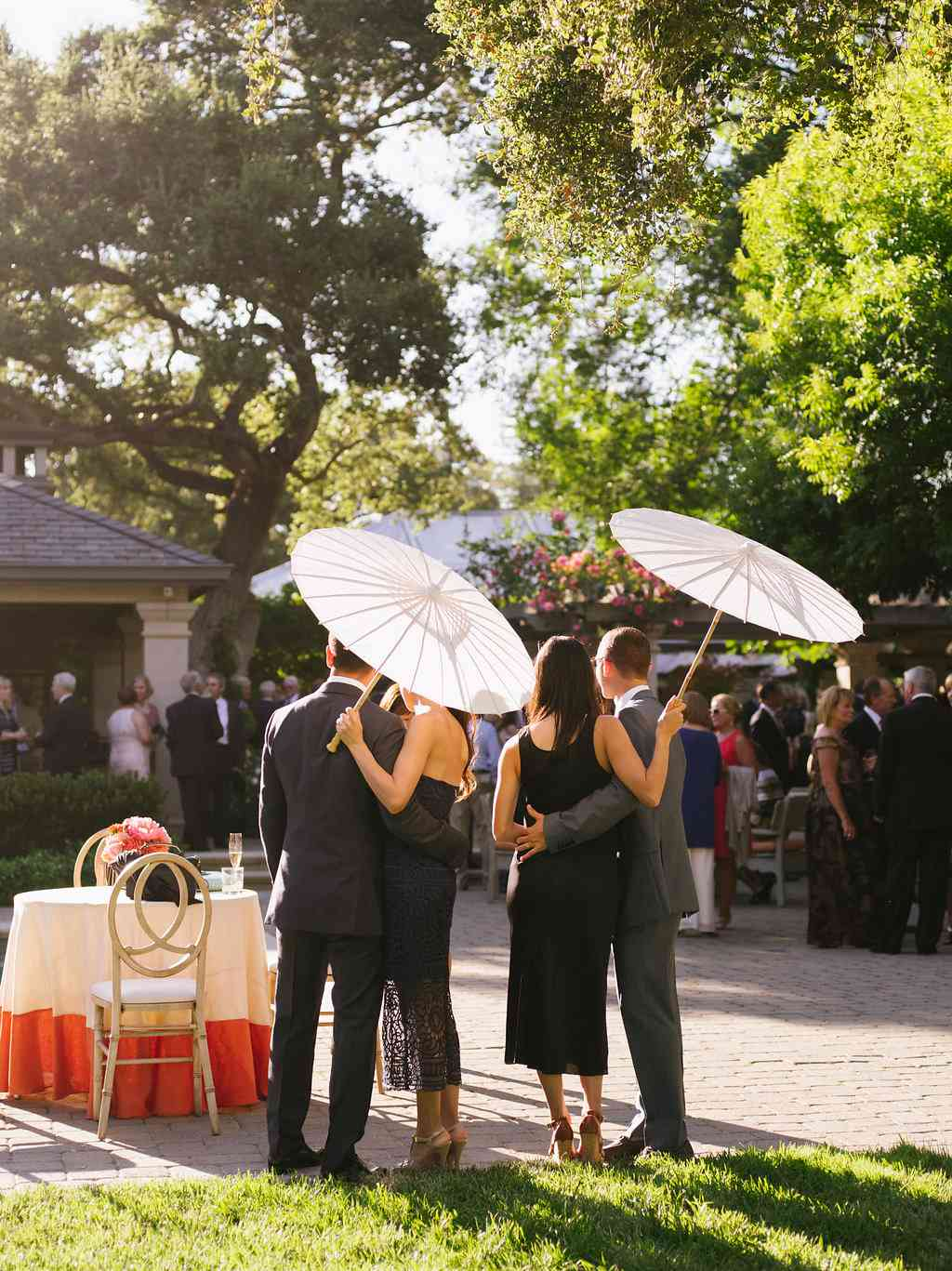 Wedding guests holding parasols at an outdoor wedding