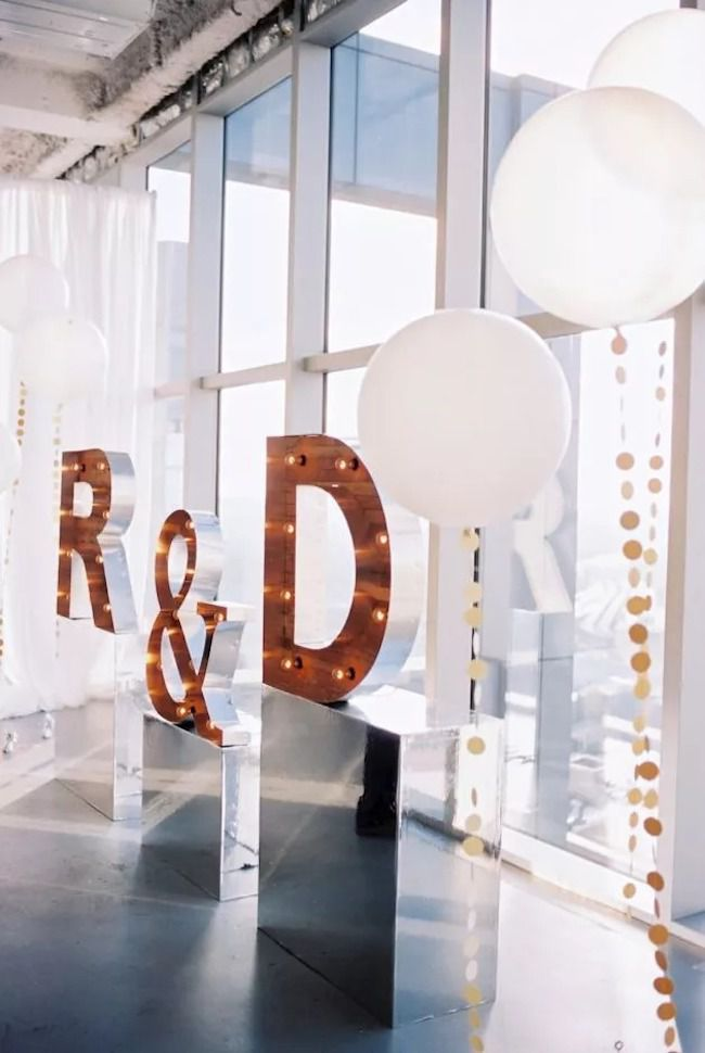Giant light-up marquee letters with oversize white balloons